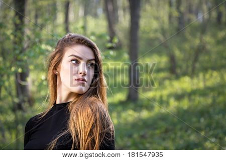 Portrait of a young blonde girl in forest looking away