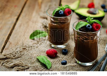 Raw vegan chocolate avocado pudding on wood background