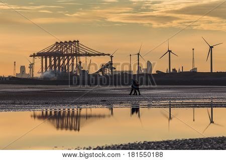 Reflections in the pools of water on Crosby beach at sunrise.