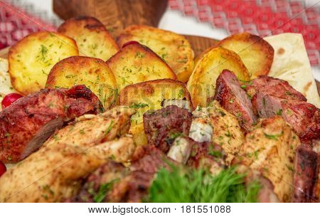 Closeup assorted barbeque plate. Grilled potato and meat platter- beef, pork ribs, chicken fillet and dill.