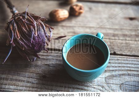 A Cup of coffee on wooden background, with flower and nuts. Romance, Breakfast in bed, compliments. Delicious beverage. and