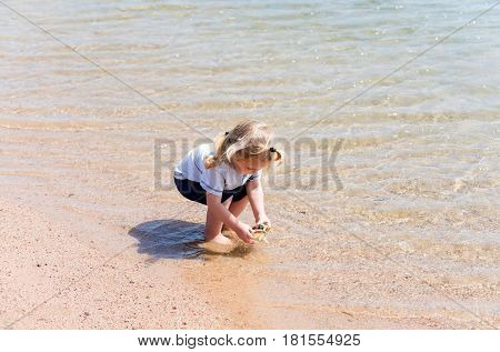 Cute baby boy small little child with blond hair playing with seashell or marine shell on beach at sea shore with crystal clear water on sunny day on sandy background. Idyllic summer vacation