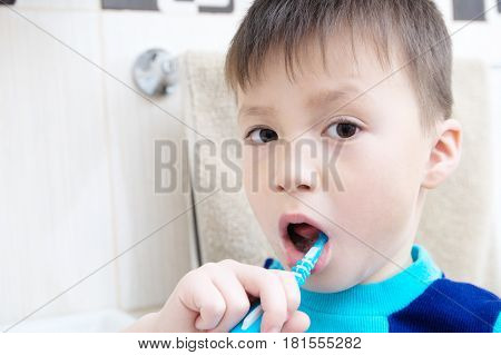 Boy portrait brushing teeth child dental care oral hygiene concept child in bathroom with tooth brushhealthy lifestyle