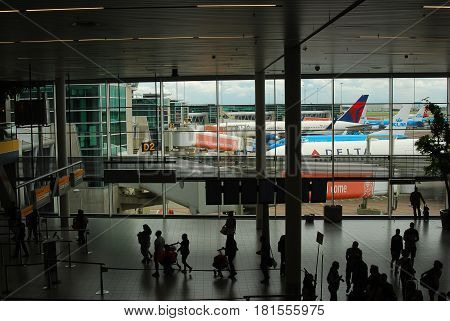 Schipol Airport ,Holland-July 31, 2016 Planes from different airlines can be seen through a window as passengers walk on a busy concourse