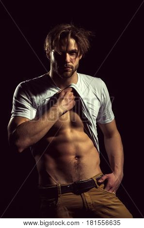 Handsome man or unshaven macho bodybuilder with stylish blond hair haircut in white tshirt showing sexy muscular torso with six packs and abs biceps triceps striptease on black background poster