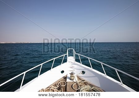 traveling and transport sport hobby fishing and yachting. white boat or ship vessel heading to horizon in sea or ocean water on sunny day on blue sky background. Idyllic summer vacation