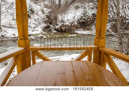 Winter rural scenery: snow covered wooden arbor .