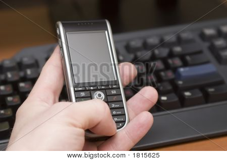Cellular Phone In Hand Of A Man On A Workplace