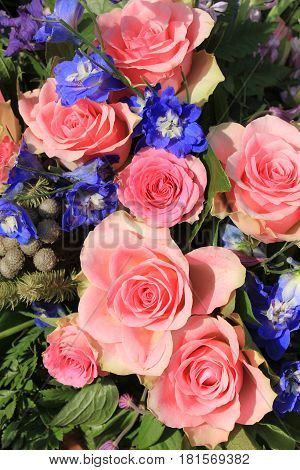 Pink roses and blue larkspur in a floral wedding decoration