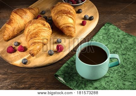 A photo of a cup of coffee with crunchy French croissants and fresh raspberries and blueberries on a wooden cutting board, with a place for text. Selective focus
