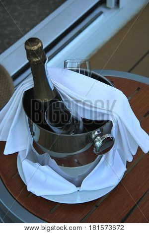 A bottle of champagne and glasses waiting in a bucket to be served