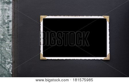 Vintage photo frame with old faded gold photo corners on black page of antique photograph album on grunge background