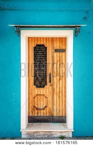 Picturesque door on blue wall of houses on the famous island Burano, Venice, Italy