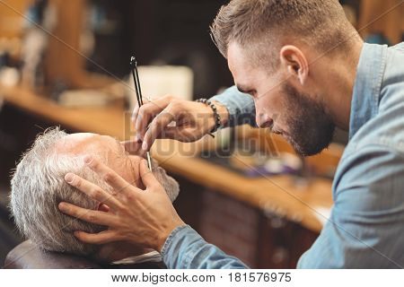 Shaving process of beard in barbershop. Serious young creative barber standing in the barbershop and shaving beard of the aged client while using razor