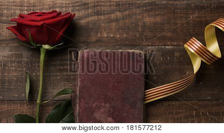 a red rose, an old book and a catalan flag, on a rustic wooden table, for Sant Jordi, the Catalan name for Saint Georges Day, when it is tradition to give red roses and books in Catalonia, Spain