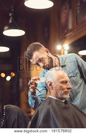 Paying attention to details. Bearded masterful concentrated master standing in the barbershop and styling hair of the aged client while combing his hair