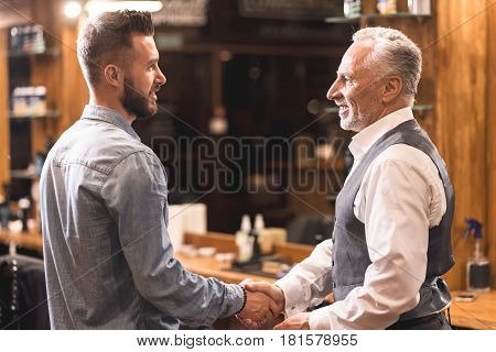 Great time at barbershop. Bearded stylish old man standing in the barbershop and handshaking with master while expressing positivity