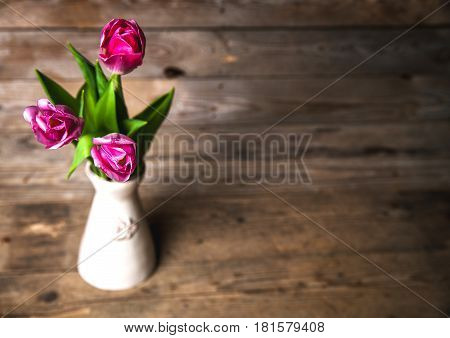 Vase of natural tulips. flowers on a wooden background and