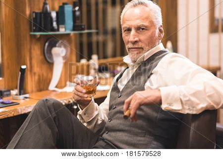 Enjoying chic life. Charismatic confident old man sitting in the barbershop and holding cigar and glass of whisky while enjoying free time
