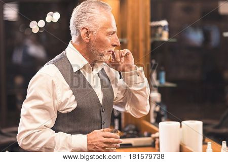 Satisfied with perfect result . Handsome stylish old client standing in the barbershop and holding glass of whisky while looking at the mirror