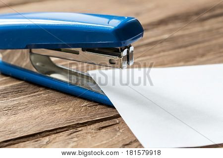 blue stapler and paper sheet on wooden background, close-up