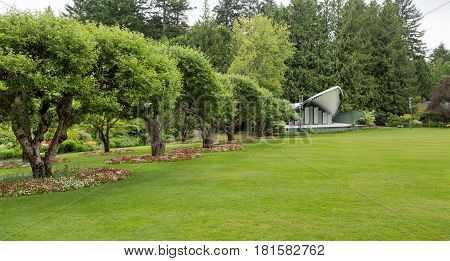 A small stage on a large green lawn in a public garden