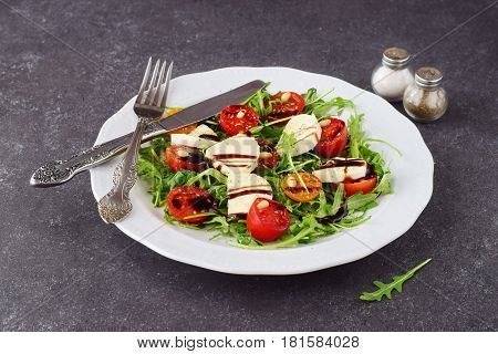 Traditional Italian salad with cherry tomato, ruccola, mozzarella, olive oil wine vinegar on a white plate on a grey abstract background.