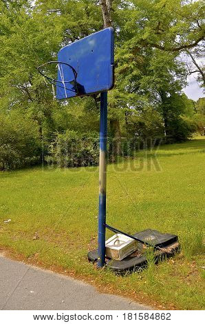 A bent rim, a missing net, and blue backboard display the memories of outdoor basketball alongside a street.