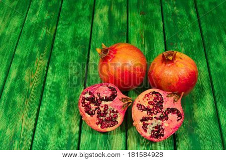The photo shows the pomegranate. Some of them are crossed, juicy pout and stones are visible. Fruits are placed on a wooden substrate made of boards painted with green paint.