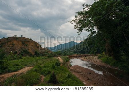 Landscape with riverbed with low water in the rain forest of Khao Sok sanctuary Thailand