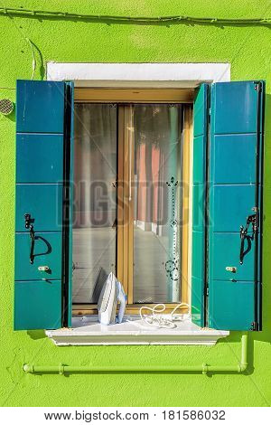 Picturesque window with flatiron on green wall of houses on the famous island Burano, Venice, Italy