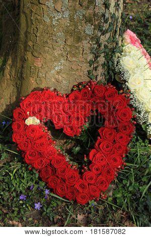 Heartshaped sympathy flowers or funeral flowers near a tree