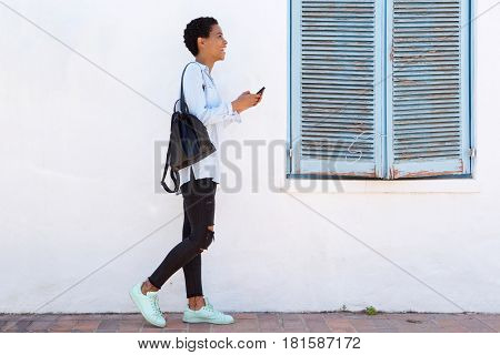 Full Length Young Woman Walking With Cellphone And Bag
