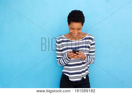 Happy Black Woman Looking At Mobile Phone By Blue Background