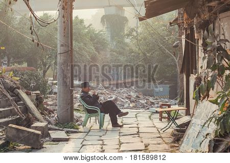 25Dec 2015ChinaChongqing : a man sitting on a chair in front of bricks and undevelopment place beside the famous travel attractions Ciqikou city of ancient and historical shophouses
