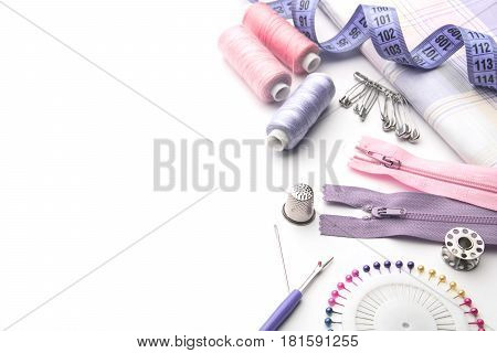 Sewing supplies and accessories for needlework. Fabric spools of thread scissors and thimbles on white background.