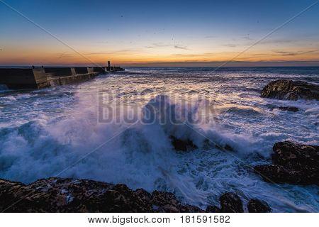 Sunset over ocean seen from breakwater in Porto Portugal