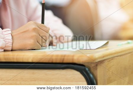 students hand holding pencil fill in Exam carbon paper sheet or test paper on wood desk
