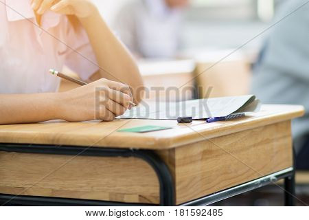 students writing test exam on paper for Admissions in high school with uniform student in School classroom of Thailand exam student background and education concept: education concept