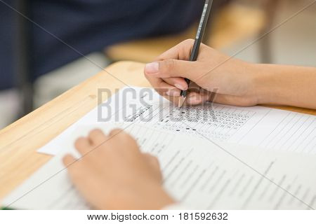 students hand holding pencil fill in Exam carbon paper sheet or test paper multichoice on wood desk education concept