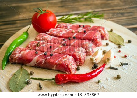 Raw cevapcici dish of mixed meats, the food of the Balkans. Minced meat and bacon.