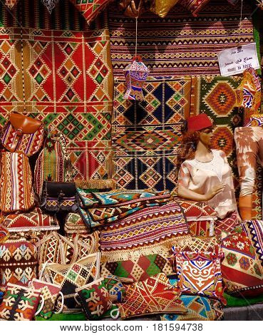 Varied display of traditional richly patterned carpets, rugs, cushion-covers, other textile souvenirs on sale in Khan al-Khalili bazaar, Cairo, Egypt