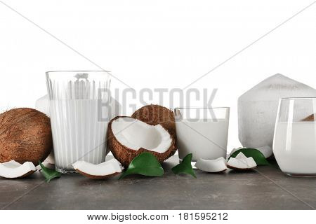 Glasses of coconut milk with nuts on white background