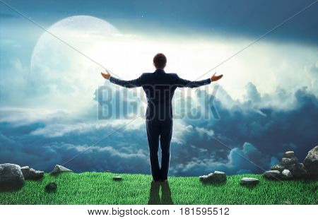 Concept of achievement of success. Standing man with raised arms on sky background. Concept of power.