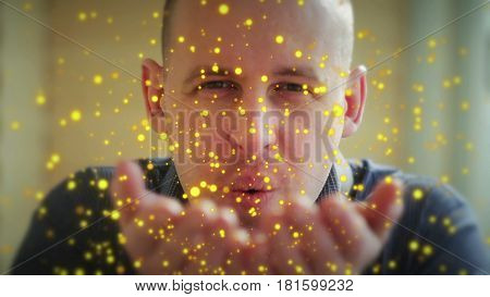 a young man blows off his hands with beautiful colored particles