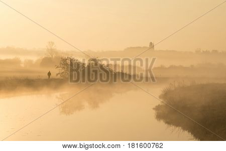 Man walking along the banks of River Nene with mist hanging over the surrounding fields at Woodford Lock in Northamptonshire England at sunrise with a church spire in the distance.