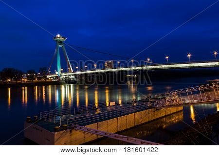 Twilight on the banks of the Danube River in Bratislava as cars travel over the UFO Bridge.