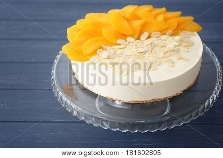Tasty cheesecake with fruit slices and nut chips on stand