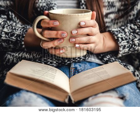 girl having a break with cup of fresh coffee after reading books or studying and