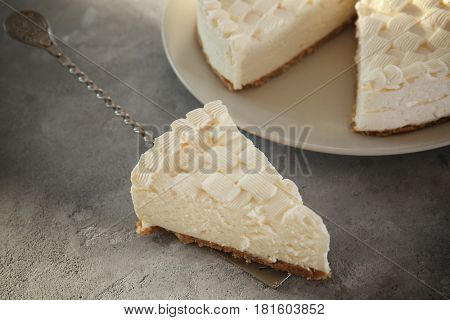 Shovel with slice of delicious cheesecake on grey table